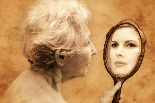 Elderly-woman-holding-hand-mirror-reflecting-young-woman